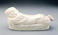 Ting Ware White Ceramic Pillow in the Shape of a Child, Northern Sung Period (960-1126).jpg